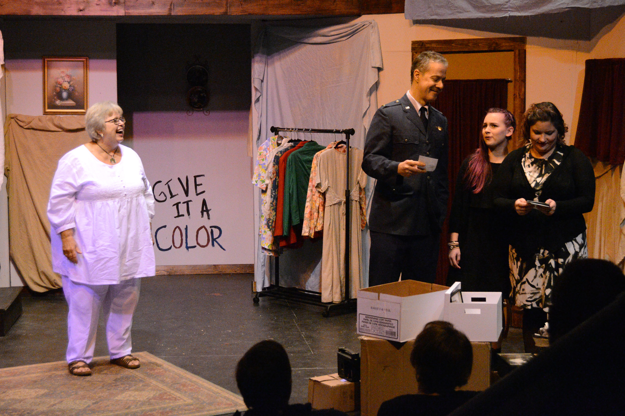 """Lillian (Jo Ann Husslein) is delighted as family members go through possessions at her posthumous estate sale including son Windsor (Peter Gibeau), granddaughter Kelly (Brooke Denman) and niece Joanna (Abbey Reinke) in a scene from Kettle Moraine Players """"Do Not Go Gentle."""""""