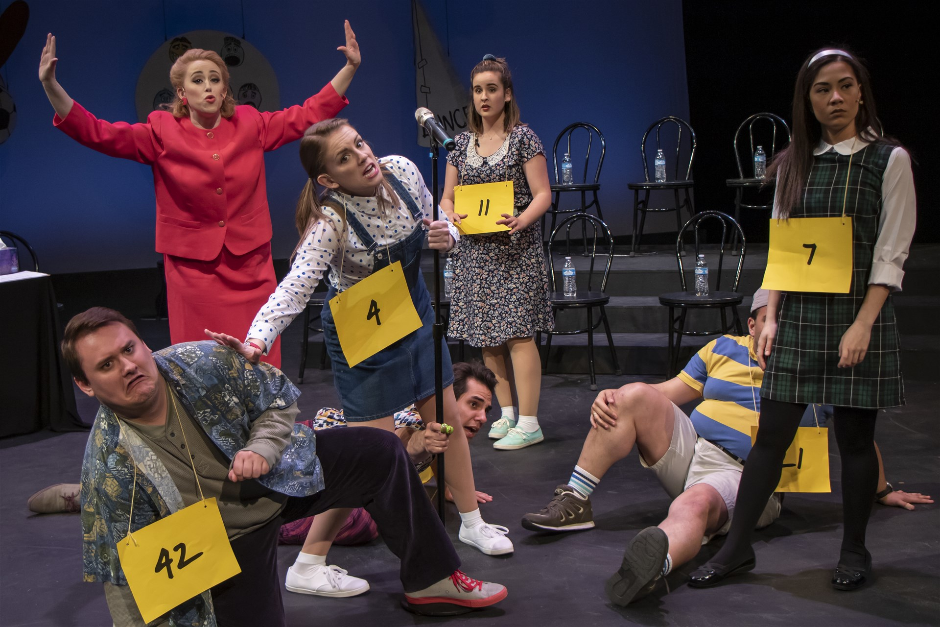 """Rona Lisa Perretti (Somantha Sostarich) tries to maintain order among the spellers at the spelling bee including, from left, William (Gage Patterson), Logainne (Sephanie Staszak), Leaf (Adam Qutaishat), Olive (Ava Bush), Chip (Romesh Alex Jaya and Marcy (Ashley Oviedo in a scene from All In Productions """"The 25th Annual Putnam County Spelling Bee."""""""