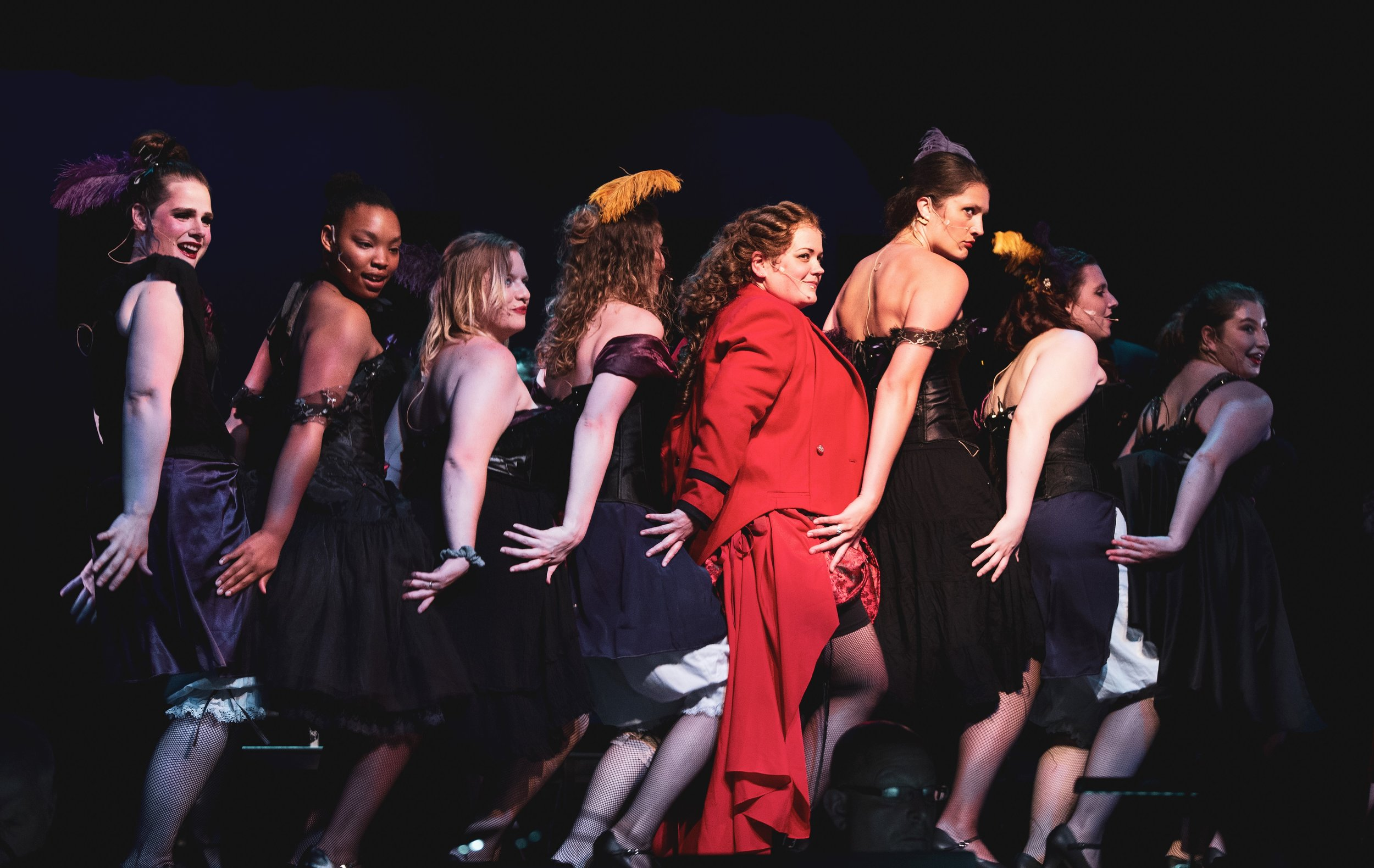 """Lucy (Gwen TerHaar in red) and the other call girls in """"Bring on the Men."""""""