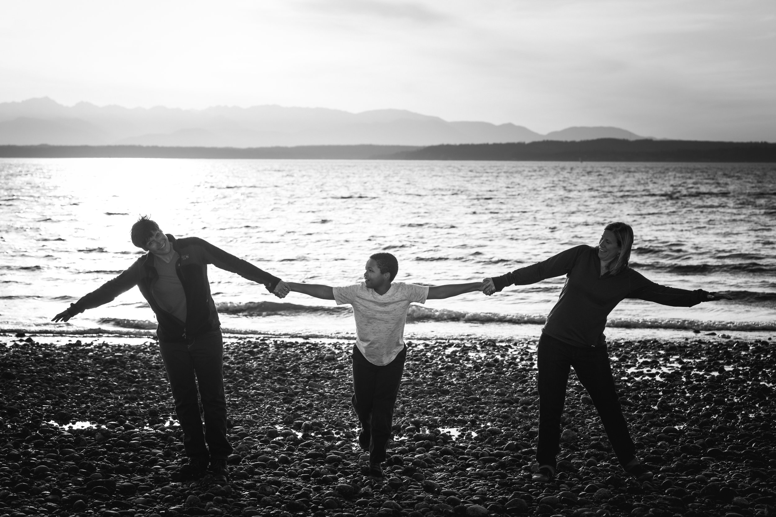 two moms and son holding hands on beach black and white