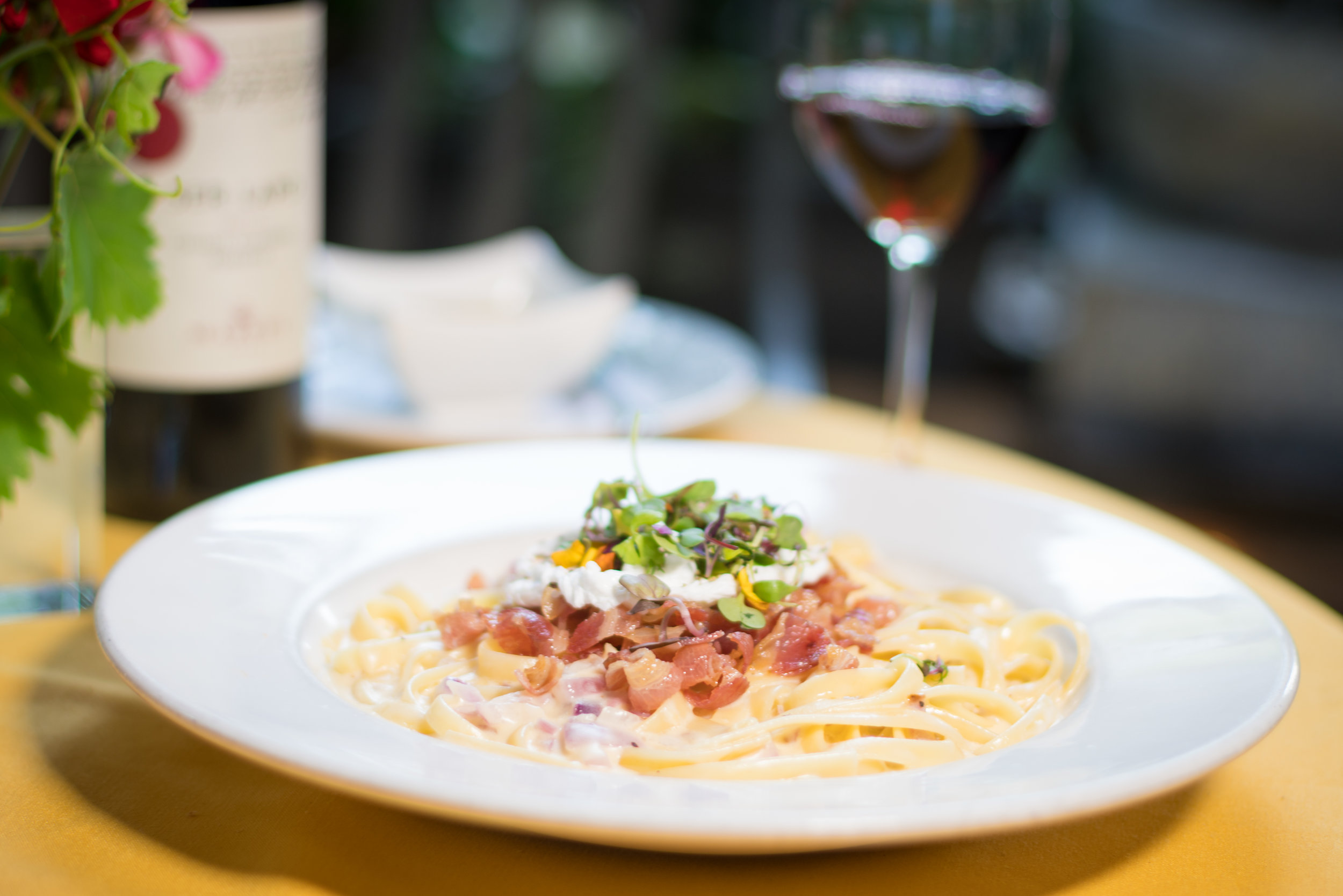 Antonio's Carbonara - Fettuccine pasta tossed in freshly made cream sauce with black pepper, onions, white wine, and topped with a perfectly poached egg and pancetta.