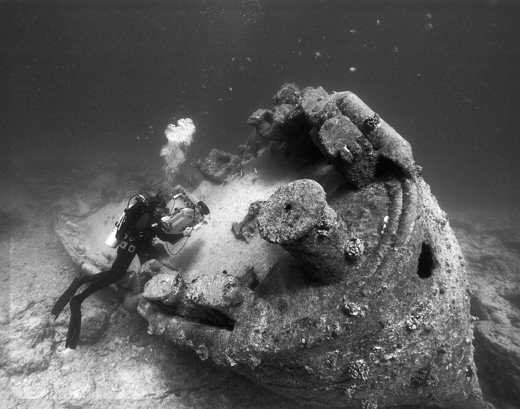 NOAA diver John Brooks inspecting the remains of the USS MACAW at Midway Island. Hawaii, Papahanaumokuakea Marine National Monument. 2005. Photo Credit: NOAA / Department of Commerce. ( This photo has been modified )