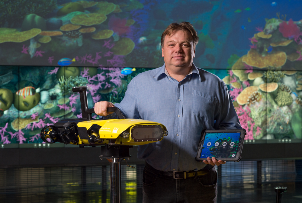 Matthew Dunbabin, Professor at QUT and inventor of RangerBot, holding the compact reef monitoring device.[Photo courtesy of QUT