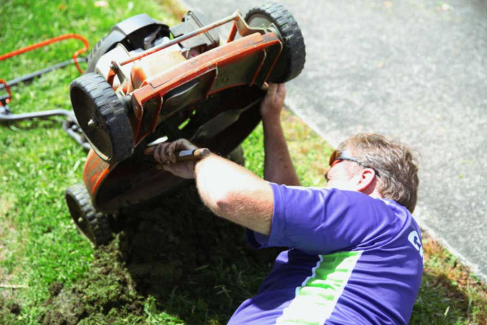 Crewcut business owner maintaining lawn mower