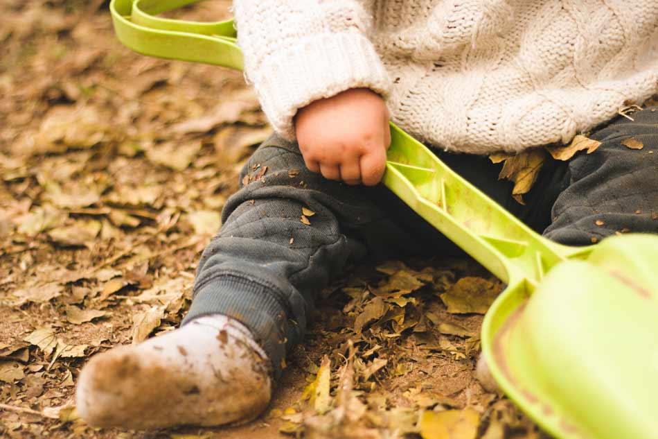 Toddler holding a plastic garden shovel