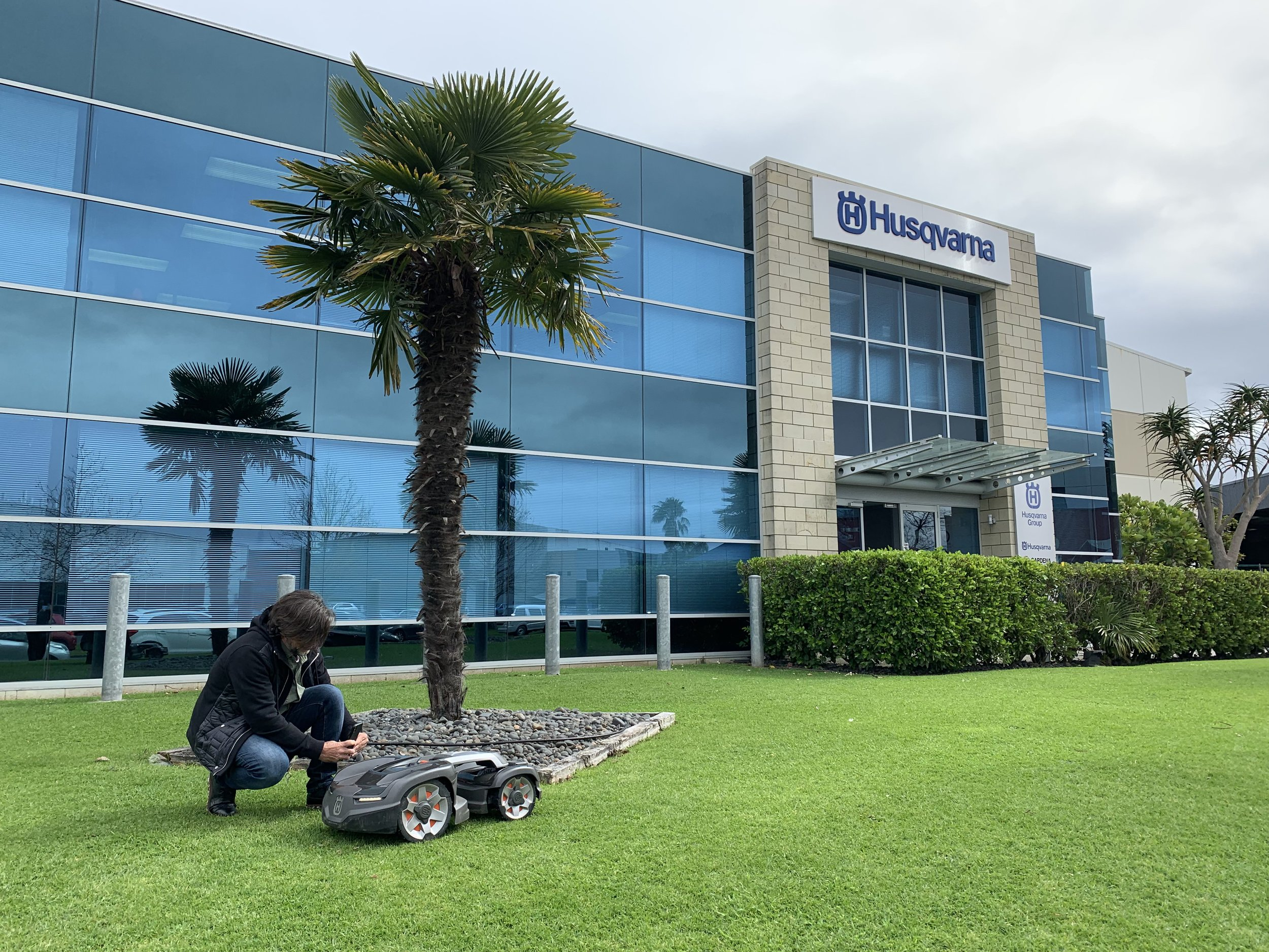 Crewcut CEO David Serville taking photos of the robotic lawn mower outside the Husqvarna office
