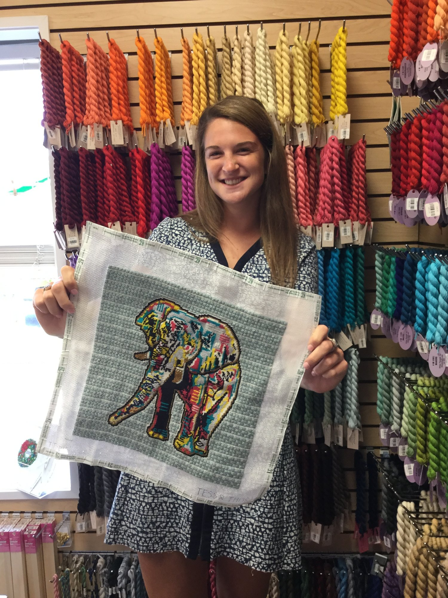 Carolyn, 19-year-old daughter of one of KC Needlepoint's co-owners, proudly displays her accomplishment, a beautiful finished canvas of a contemporary design by Thorn Alexander .