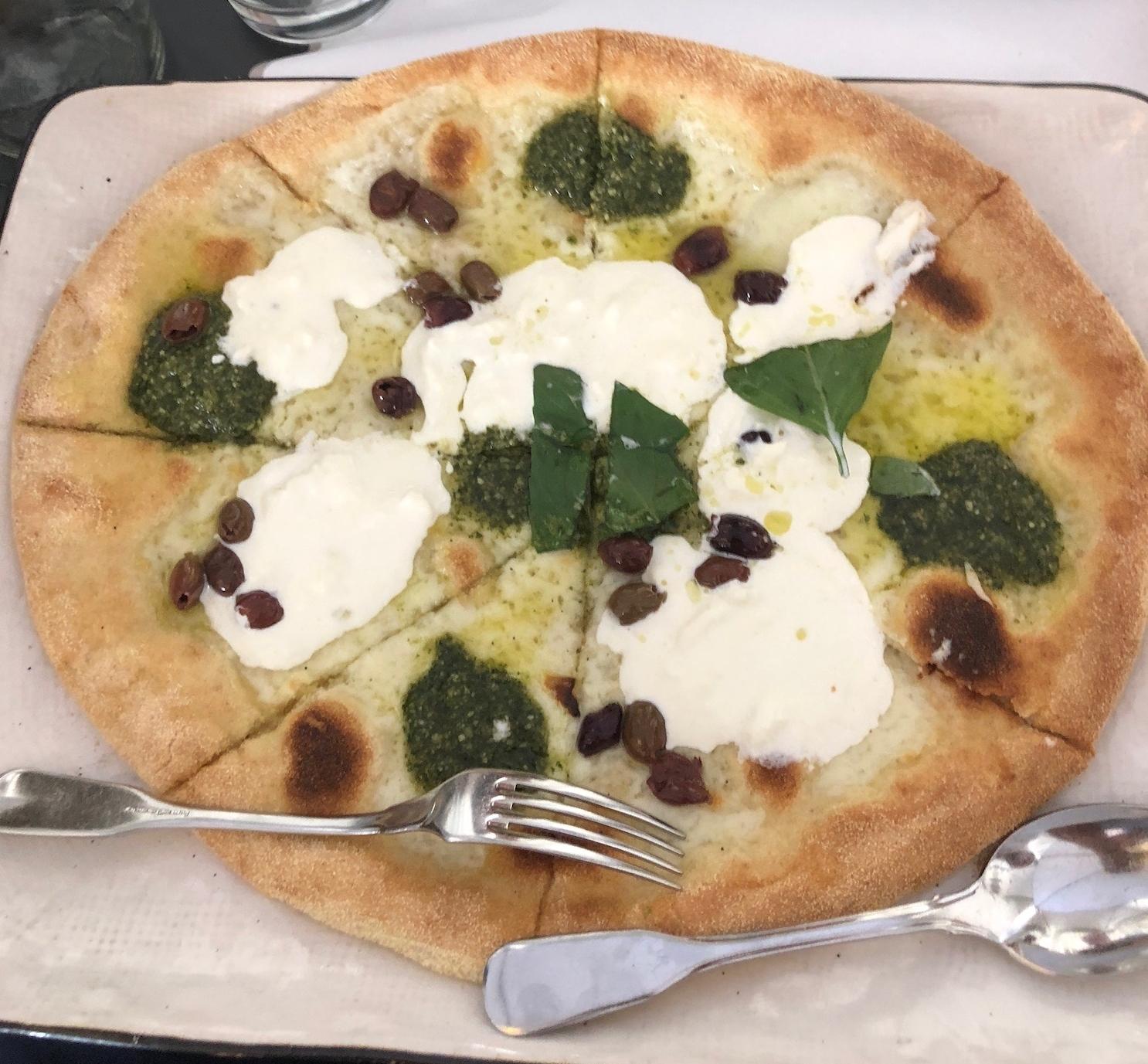 Pizza with pesto, homemade mozzarella, basil and Greek olives.