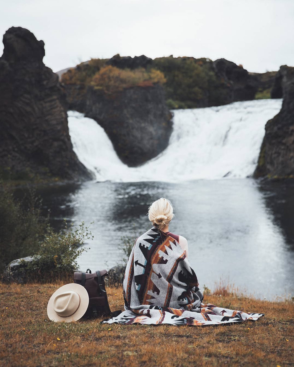 Girl traveling through Iceland with a hand stitched, full grain, vegetable tanned sustainably made leather bag by BennyBee