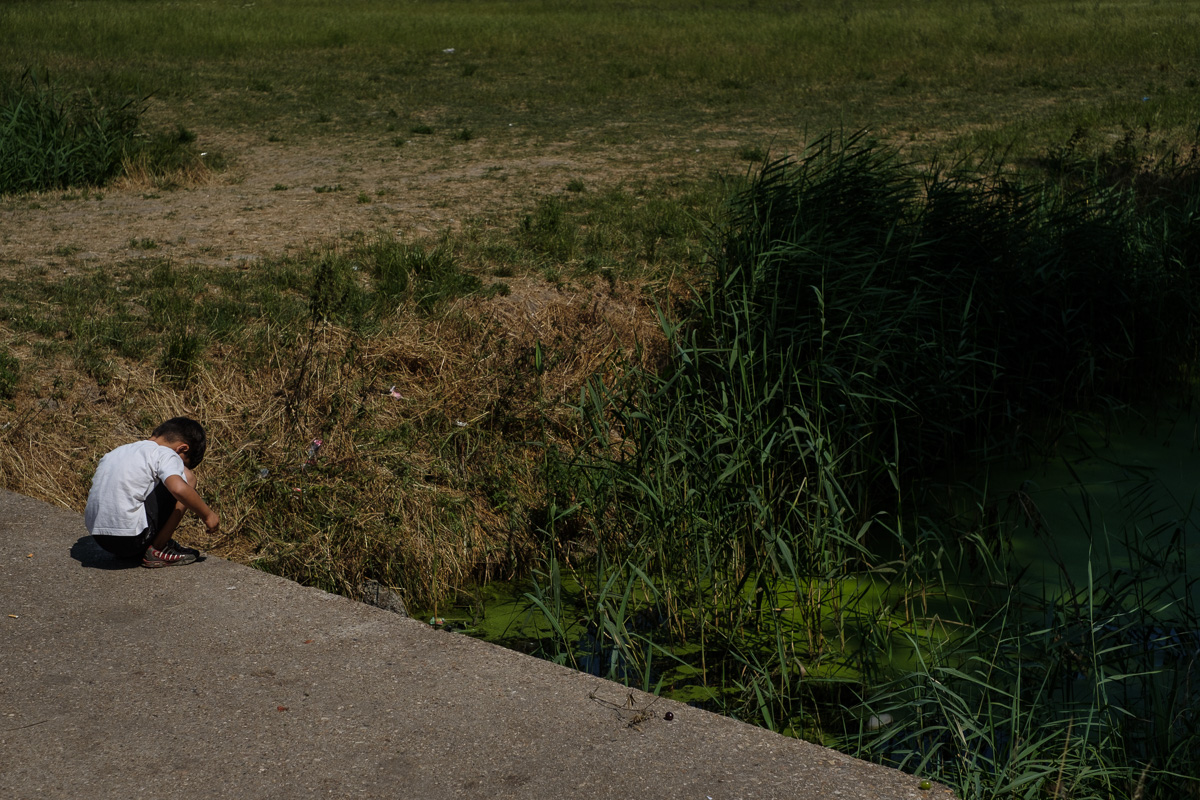 For this young migrant boy, throwing rocks in the polluted stream next to the camp is one of the only things to do.