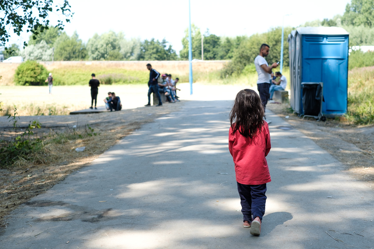 A small migrant girl on her way to the three toilets that have to serve a couple of hundred refugees.