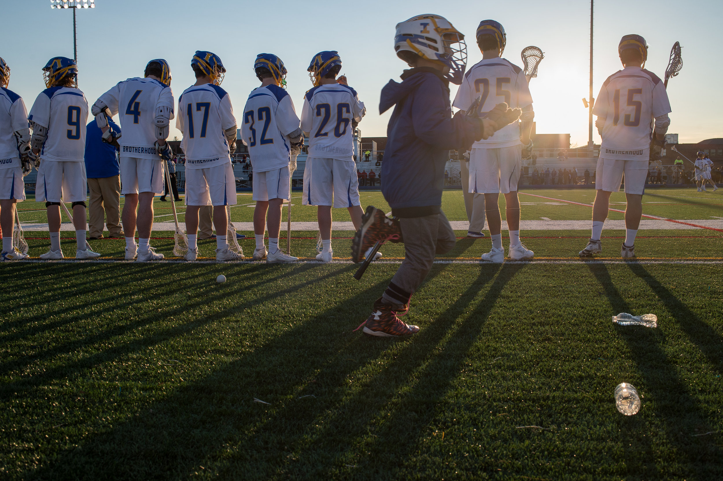 Cooper Moore runs down the sidelines of the game while the players of Irondequoit high school boys lacrosse team try and block the sun from their eyes while they watch the game, April 13, 2017. Irondequoit high school scored within the last nine seconds of the game to beat Canandaigua Academy.