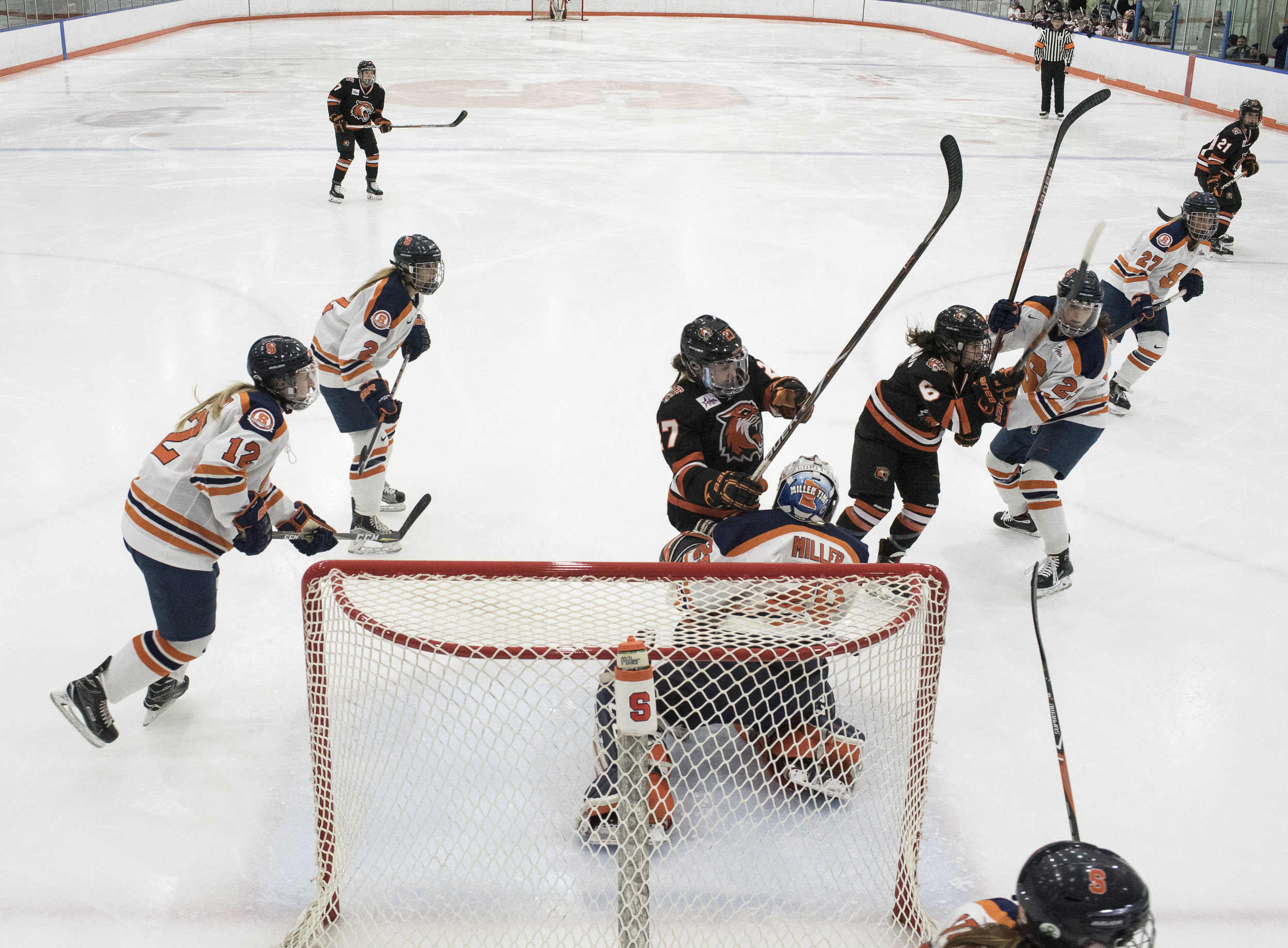 Rochester Institute of Technology's women's hockey players and Syracuse University's players turn towards the puck on Feb. 9, 2017 at Tennity Ice Pavilion, Syracuse N.Y. RIT Women's Hockey team lost to Syracuse University with a final score of (1-7).