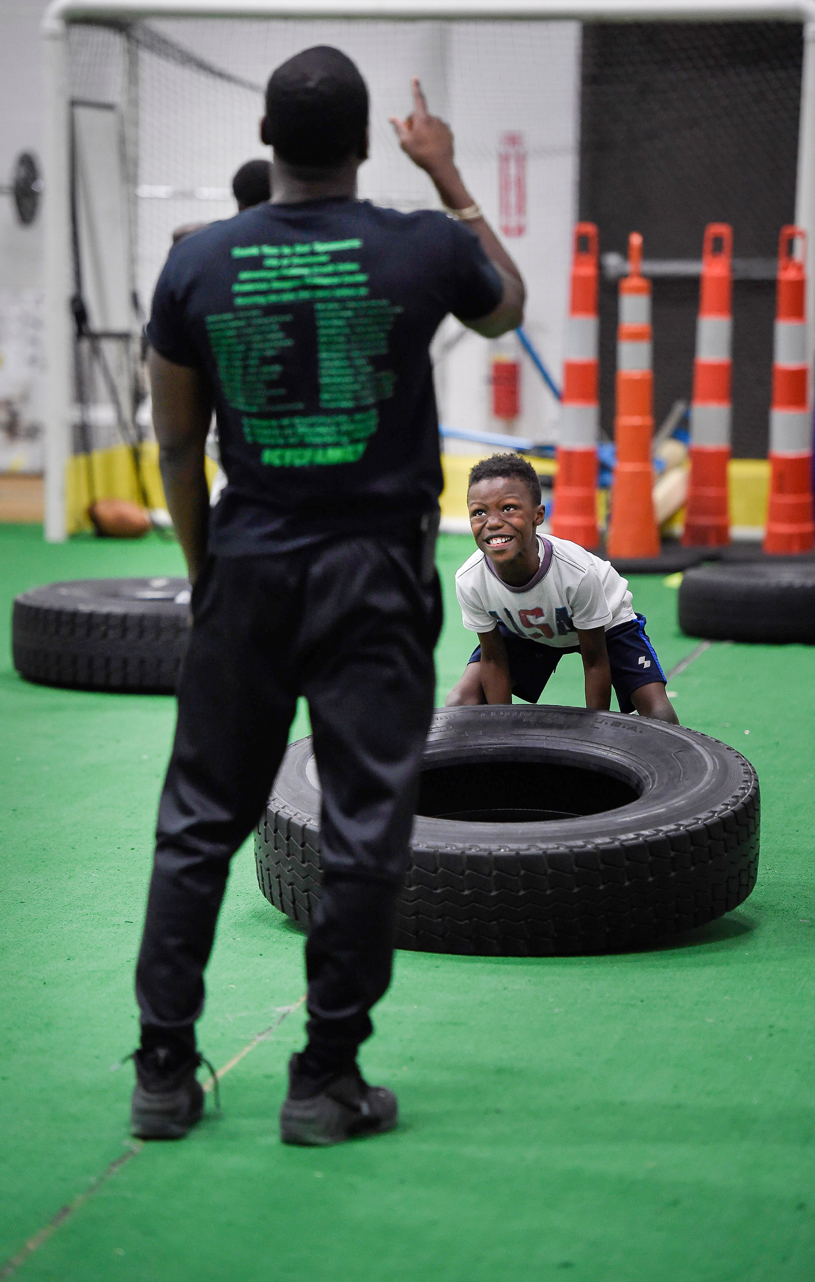 Hopkins points his finger upwards to correct an athlete's posture while he lifts a tire at Lincoln Sports Park, Dec. 7, 2017.