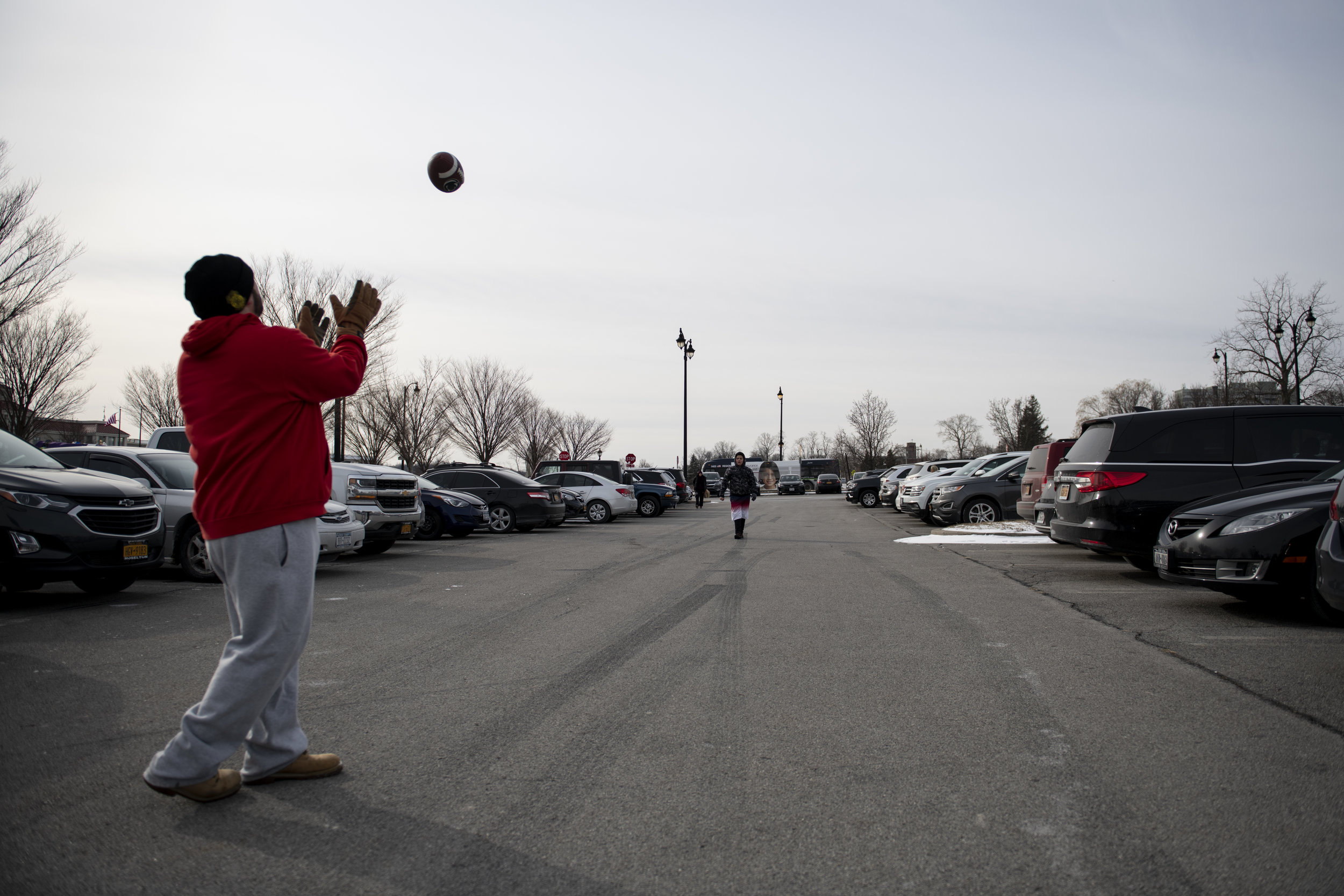 Anthony Patta catches a football from Alex Entz, age 9, in the parking-lot prior to the 2019 Polar Plunge at Ontario Beach Park in Rochester, N.Y. Feb. 10, 2019. The 2019 Polar Plunge raised over $250,000 for the Special Olympic community.