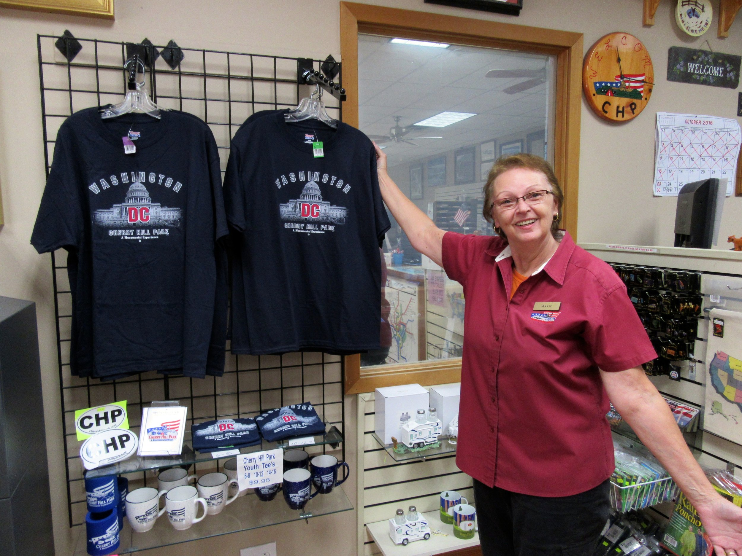 Employee Poses Next to Washington DC T-Shirts in Cherry Hill Park's Souvenir Store