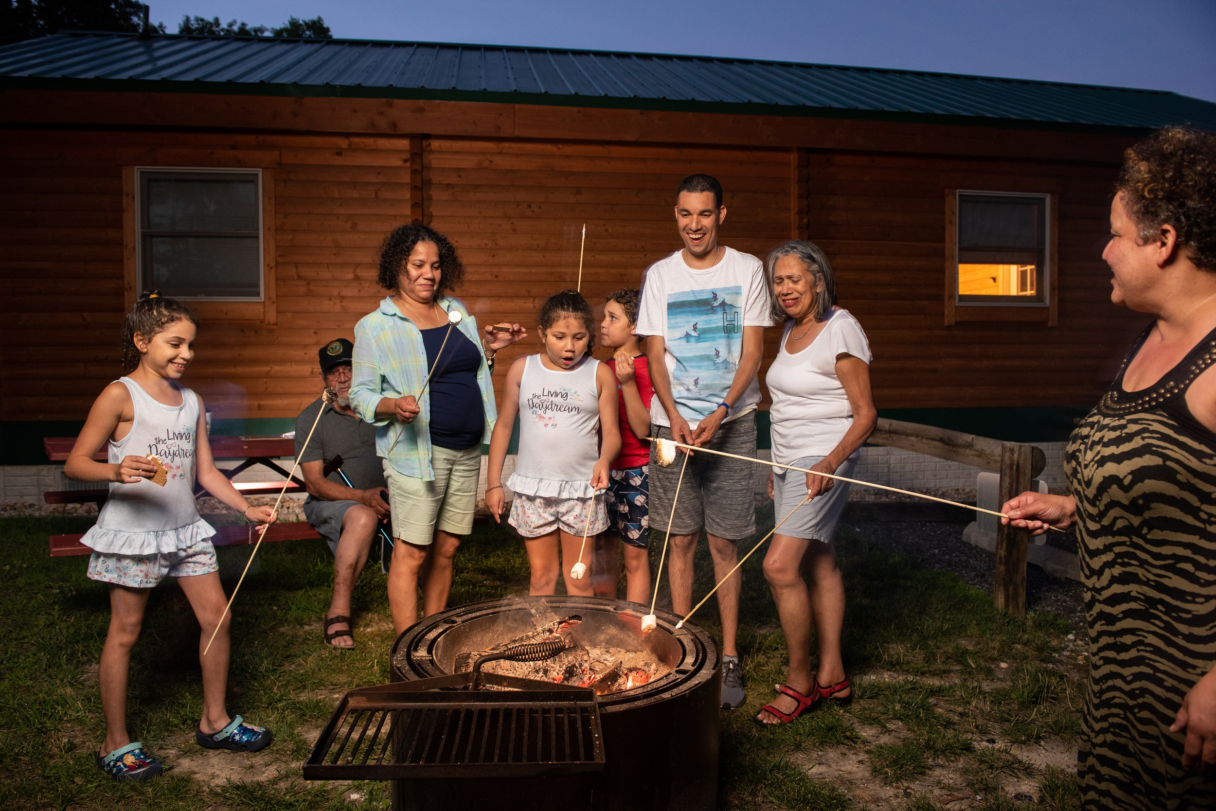 Family Roasts Marshmallows Outside while Camping in a Log Cabin