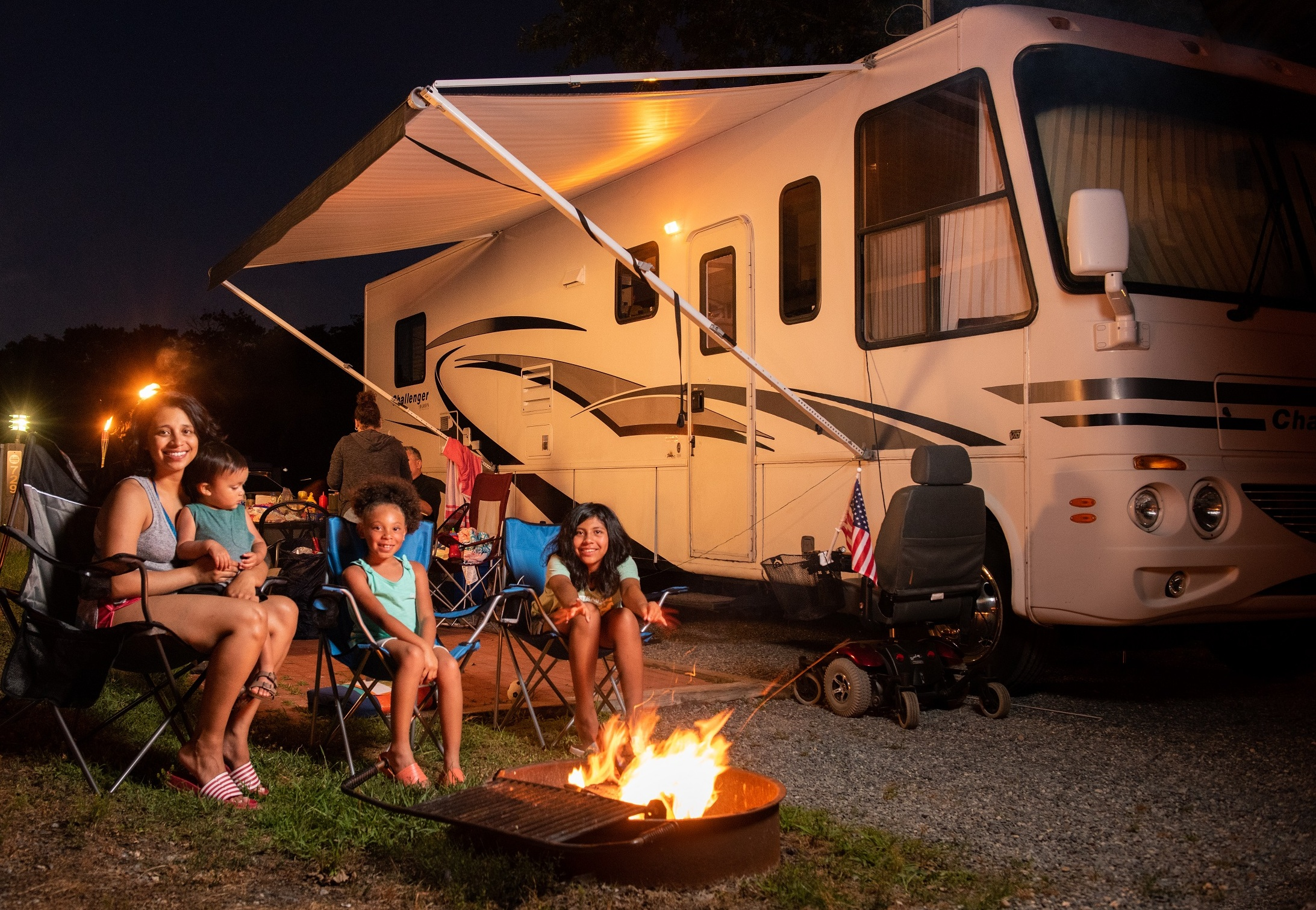 Family sits at a campfire next to their RV at Cherry Hill Park