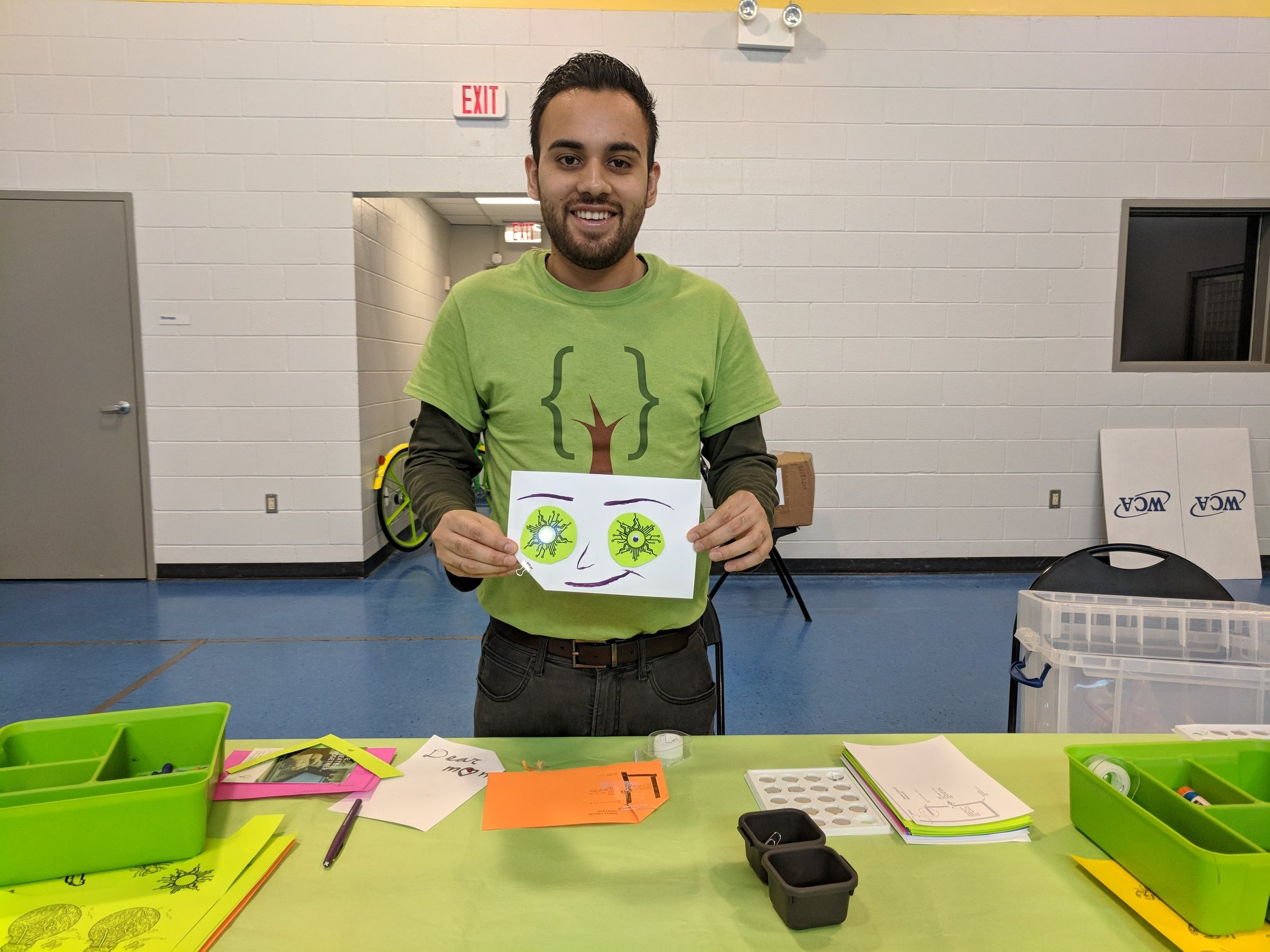 """Bryan, a volunteer and software developer at Code Park, holding his creation of a light up paper circuit card based on the idea of """"What Lights You Up?"""" card at Finnigan Park Community Center. Courtesy of Wanjun Zhang, July 7th, 2018."""