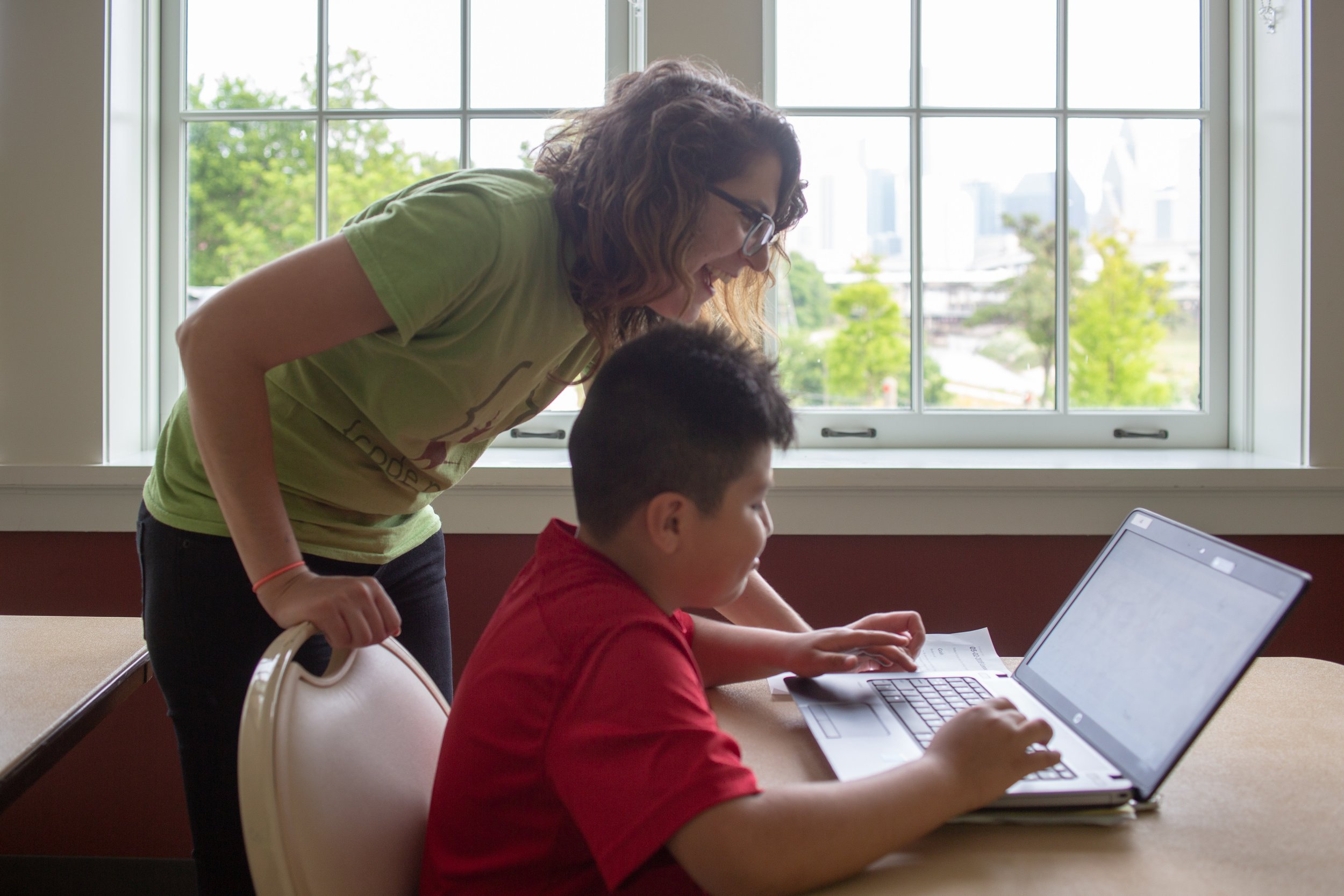 Volunteer Alex is joyful as she helps a student solves a problem. Leonel Castillo Community Center Creative Coding Code Club. Courtesy of Wanjun Zhang. May 4th, 2018.