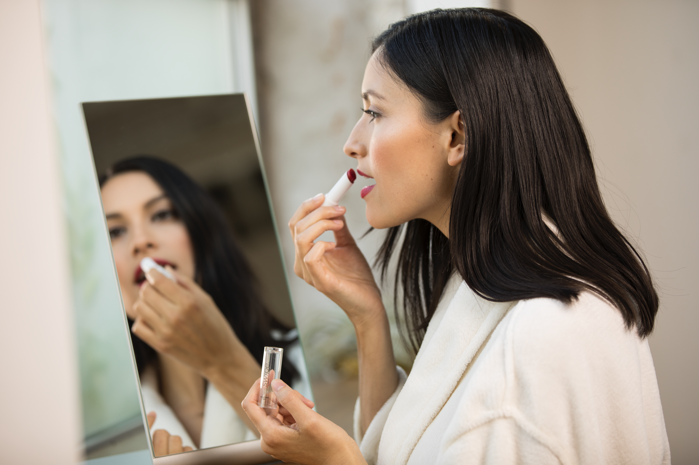Perfectly Posh Swipe Moisture Tint plumping model's lips in mirror with fluffy white bathrobe, best lip routine for pampered lips