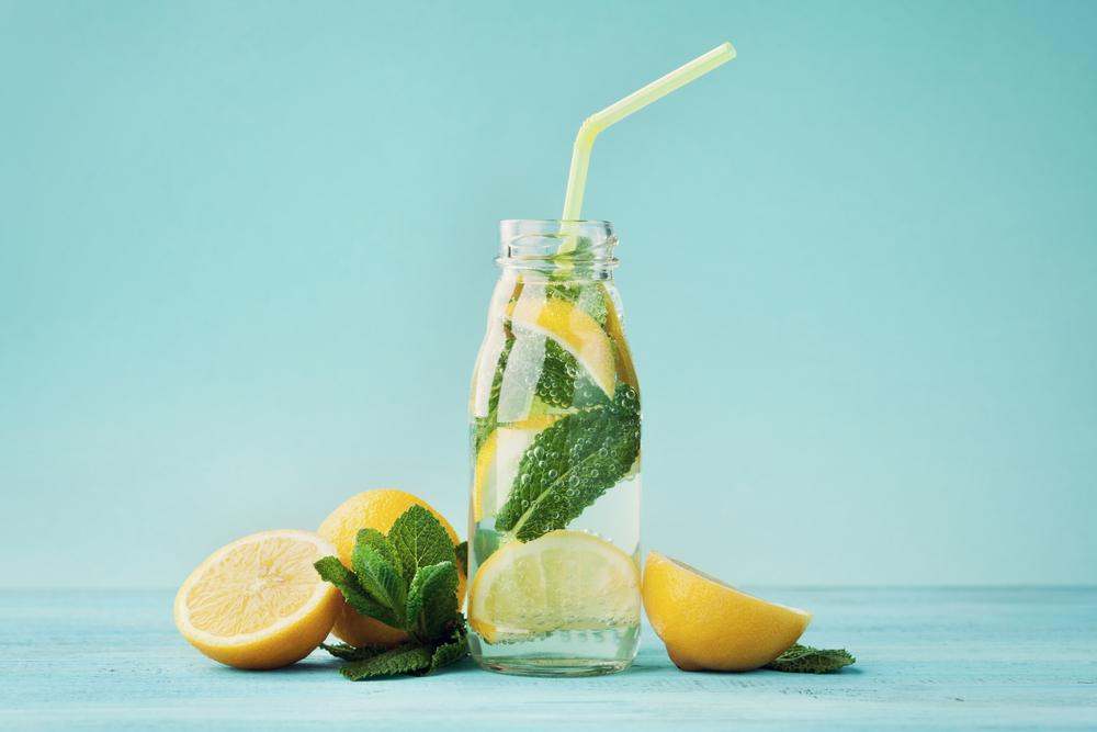 Glass of lemon water with fresh mint on blue background