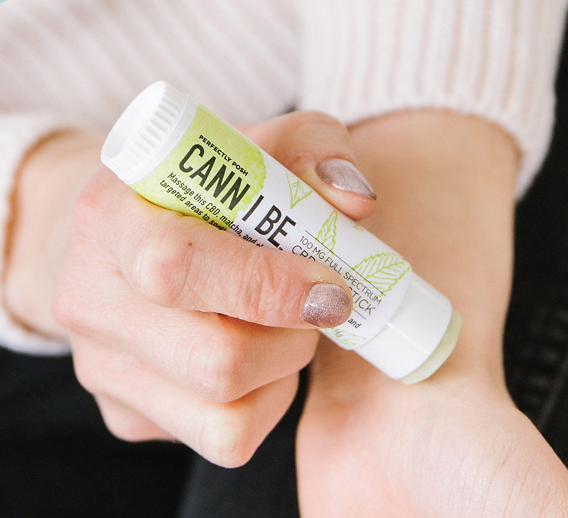 Using Perfectly Posh Cann I Be 100 mg full-spectrum CBD oil Skin Stick on wrist, close up of Cann I Be Skin Stick
