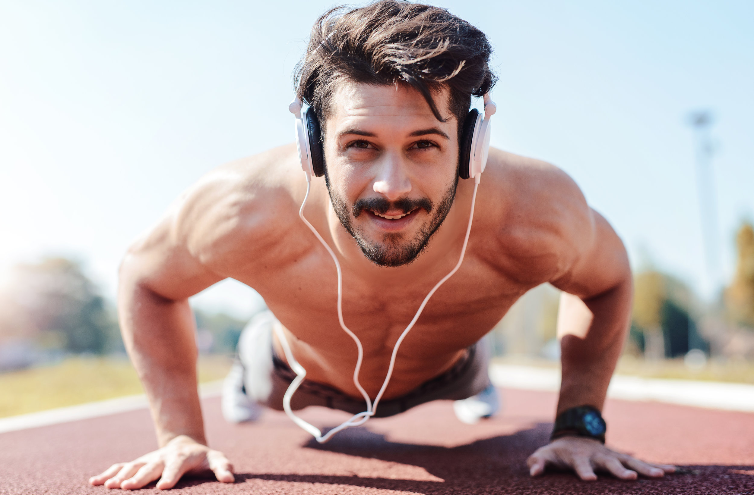 Buff guy with headphones does push ups, skincare routine for guys who like to work out