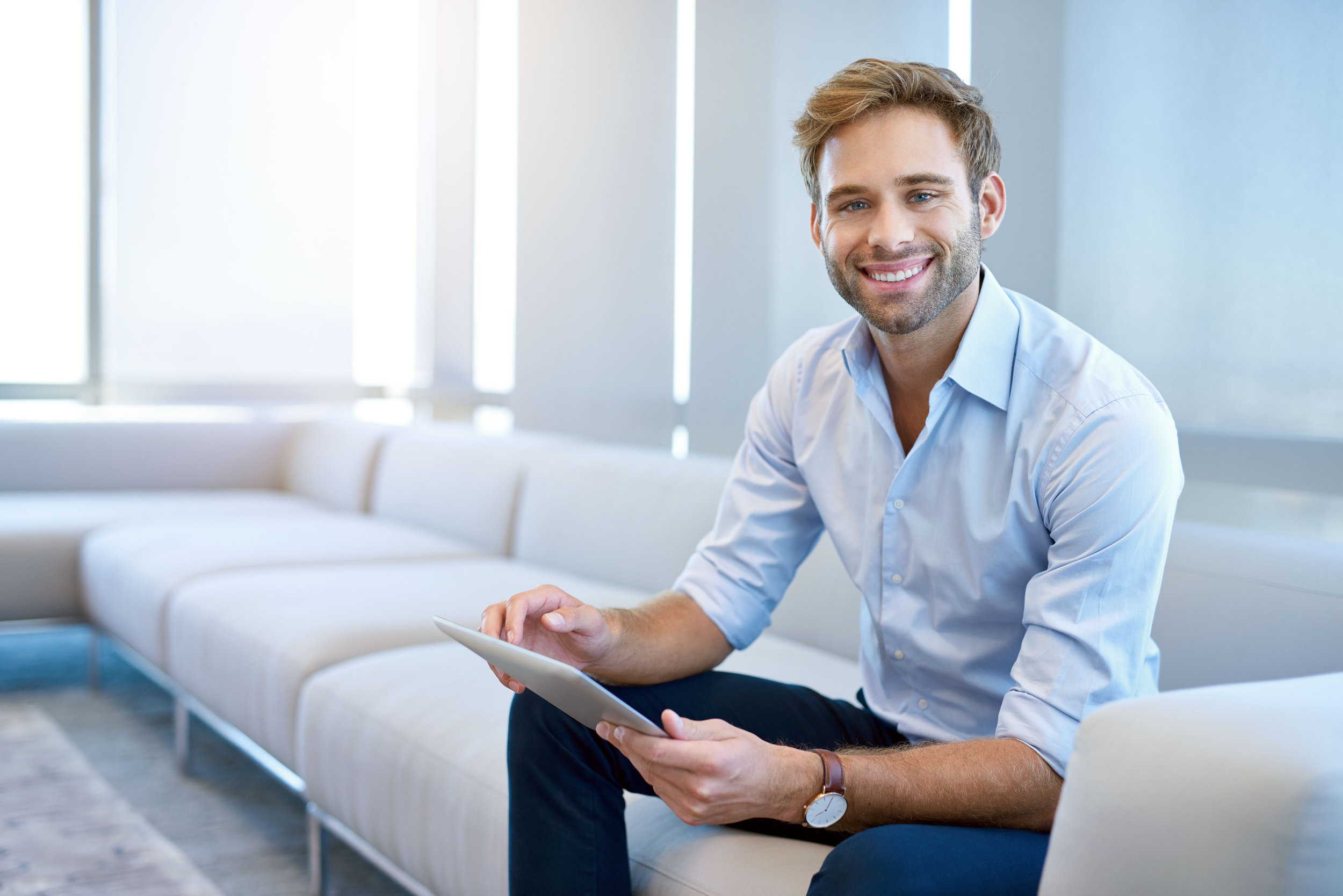 Business man with tablet on couch, men's skin care routine for business man