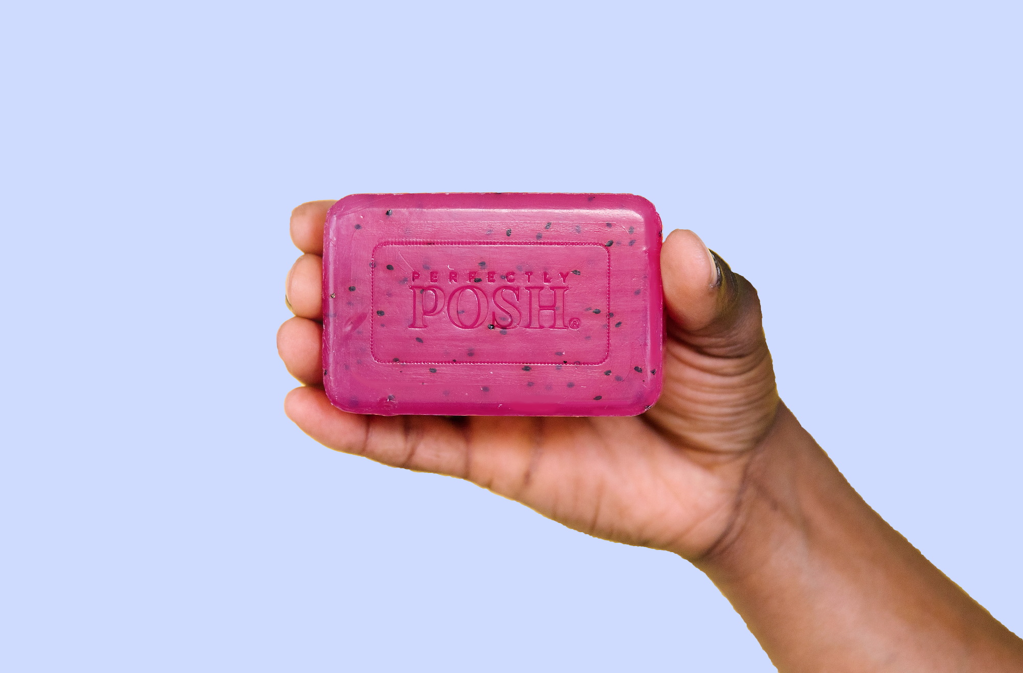 African American man holding Perfectly Posh Pink Kimono Chunk Big Bath Bar with pink dragonfruit for skin