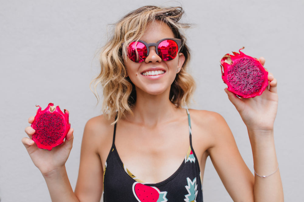 Young woman with shoulder-length blonde curls wearing sunglasses and holding pink dragon fruit cut in half for benefits of dragon fruit for skin