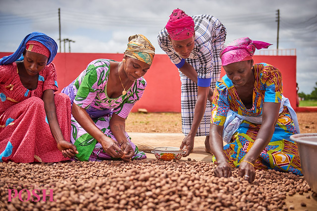 4 women from the Shea Sisterhood sort and dry shea nuts in Ghana for sustainably sourced shea butter Perfectly Posh products.