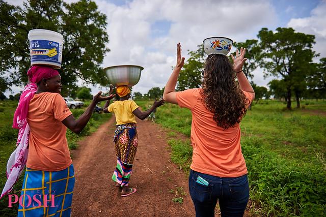Women of the Shea Sisterhood in Gizaa Gunda, Ghana carry shea nut on their heads back to the village to make sustainable shea butter.