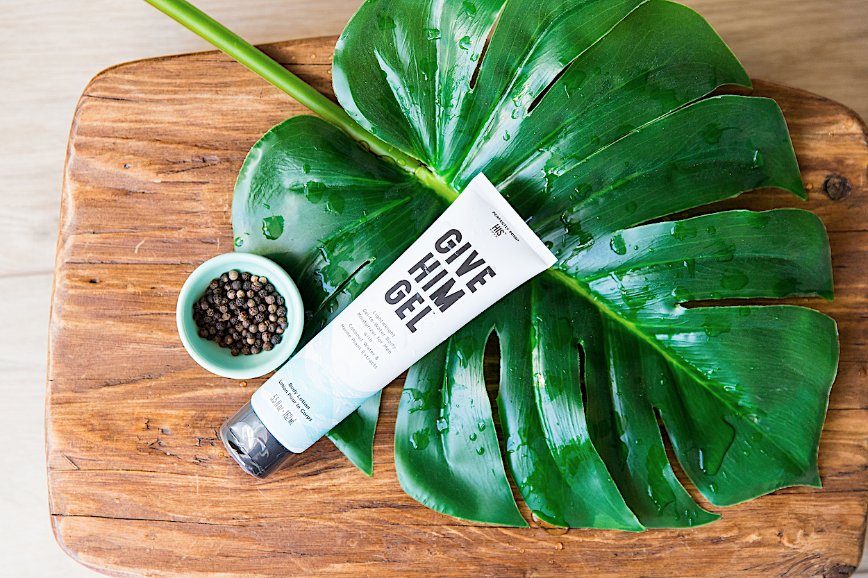 Perfectly Posh Give Him Gel Gel-to-Water Body Moisturizer for Men for hydrated skin stylized on tropical palm leaf and driftwood with water droplets