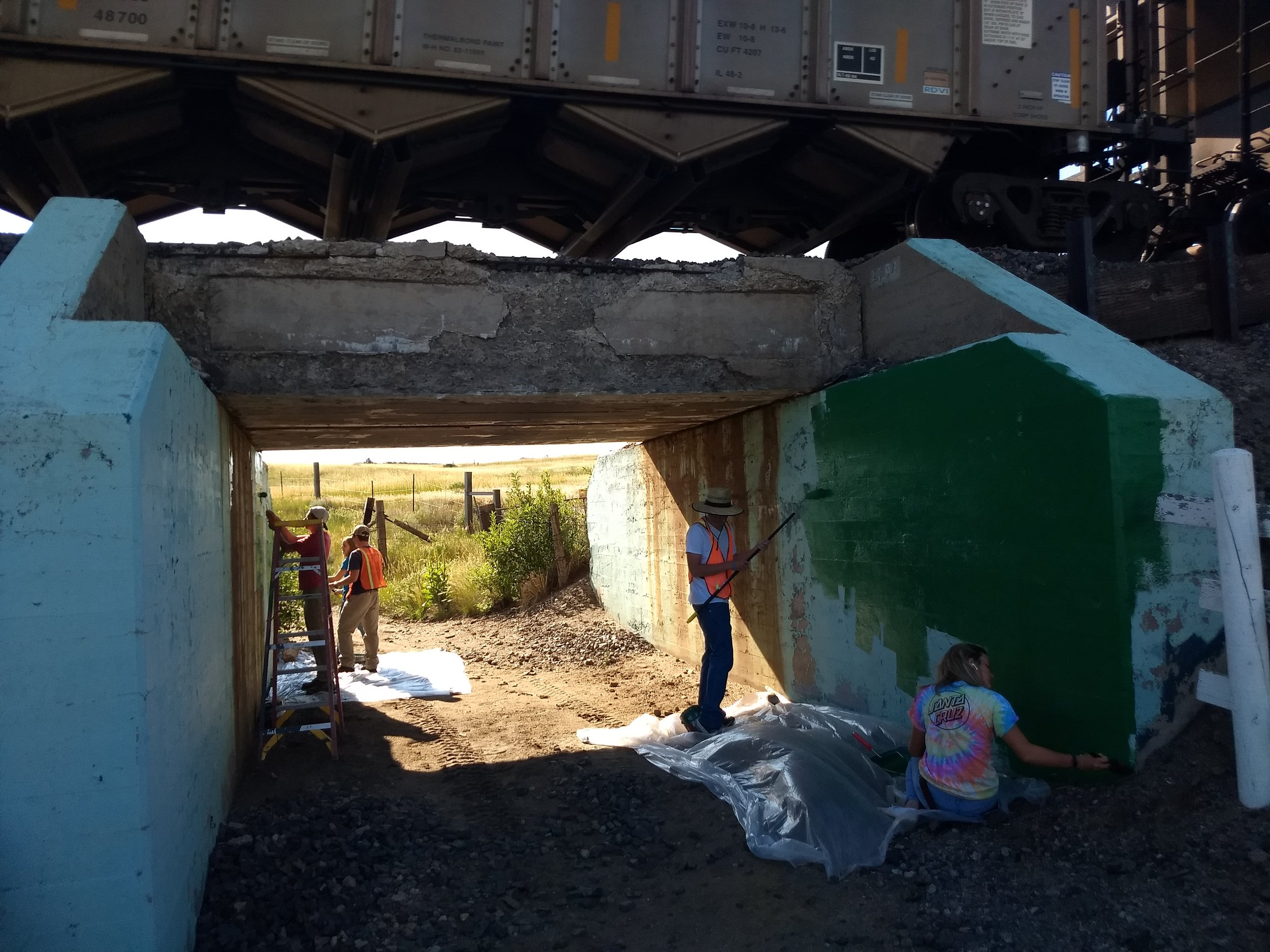 A train passing overhead while the team is painting.