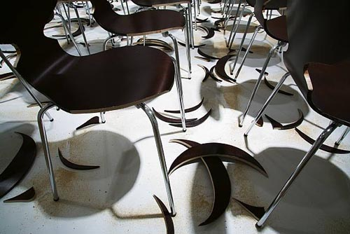 SUPERFLEX, Copy Right (detail), 2006, Eighty brown chairs, sawdust, wood cut-outs & platform
