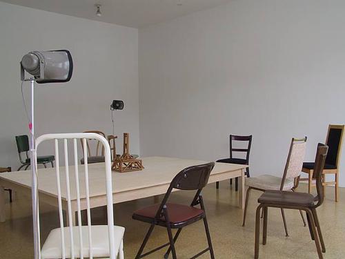 Liliana Moro, Un Mondo Senza Testa, 2003, 12 chairs, 1 table, 3 loud speakers, paper model, CD, CD player, amplifier