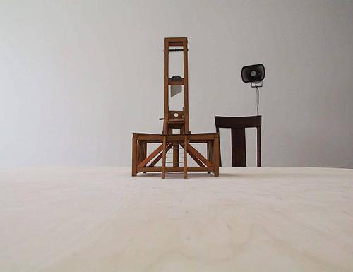 Liliana Moro, Un Mondo Senza Testa (detail), 2003, 12 chairs, 1 table, 3 loud speakers, paper model, CD, CD player, amplifier