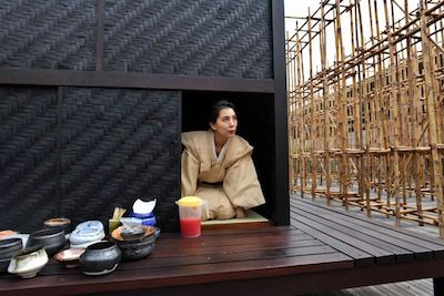 Japanese tea ceremony performance artist Mai Ueda looking out from a wooden tea house, part of a bamboo maze installation display by artist Rirkrit Tiravanija, on the roof of the National Gallery Singapore. PHOTO: AFP
