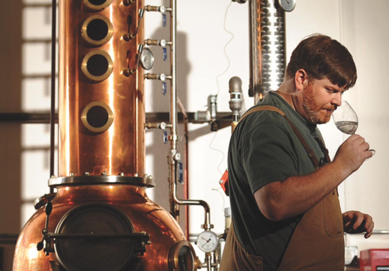 Todd Leopold, of Leopold Brothers, sniffs a sample as he distills juniper for Gin. The Denver Post/Getty.