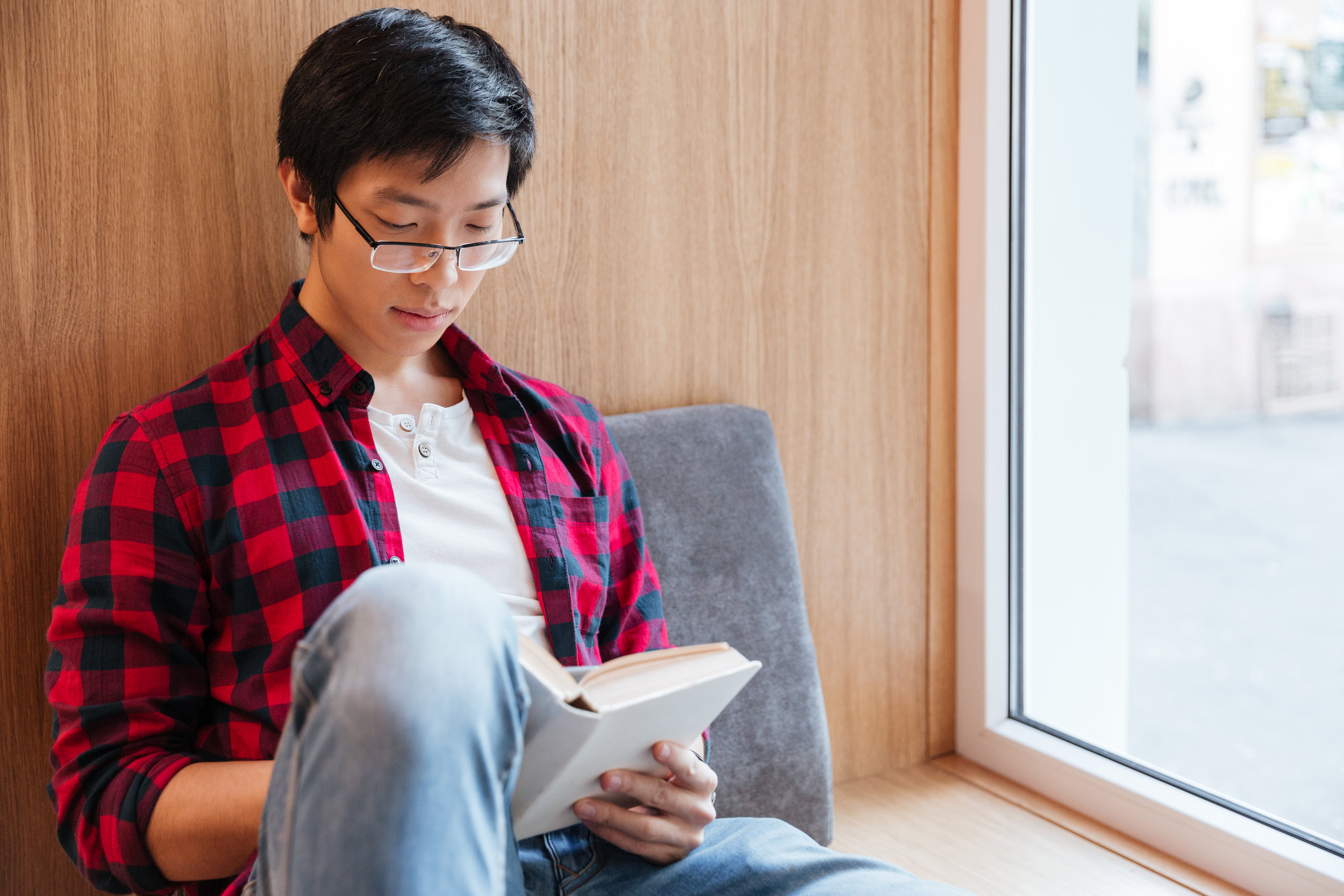 graphicstock-photo-of-cheerful-asian-student-reading-a-book-in-university-library-sitting-on-sofa_B_eS23O8hx.jpg