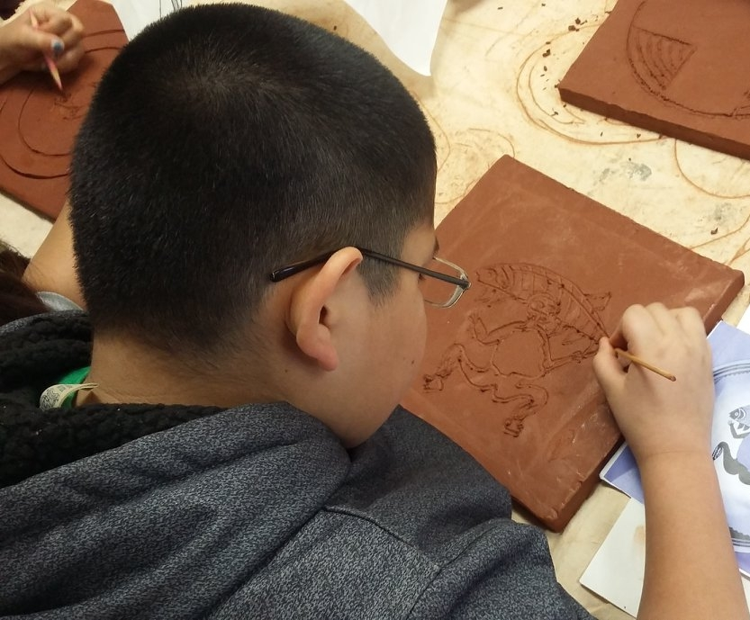 Student working on a tile for a Youth Mural project at the Visitor's Center