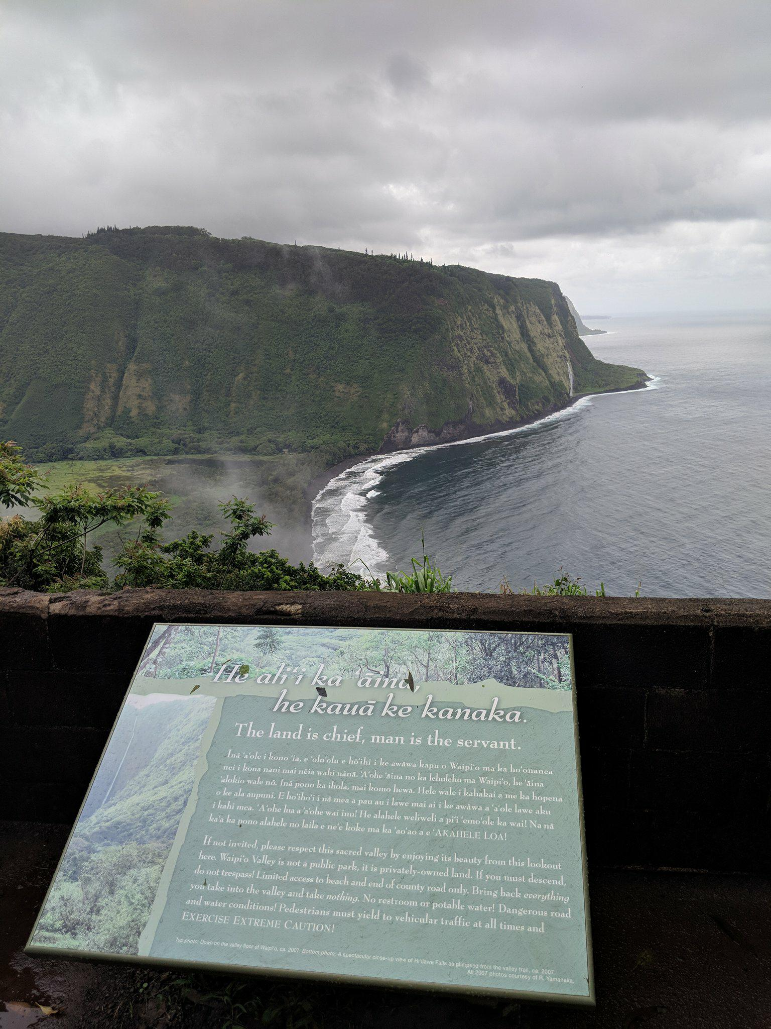 """Image Description: Waipi'o Valley with Placard reading, in part: """"If not invited, please respect this sacred valley by enjoying its beauty from this lookout here. Waipi'o Valley is not a public park, it is privately-owned land. If you must descend, do not trespass!"""""""