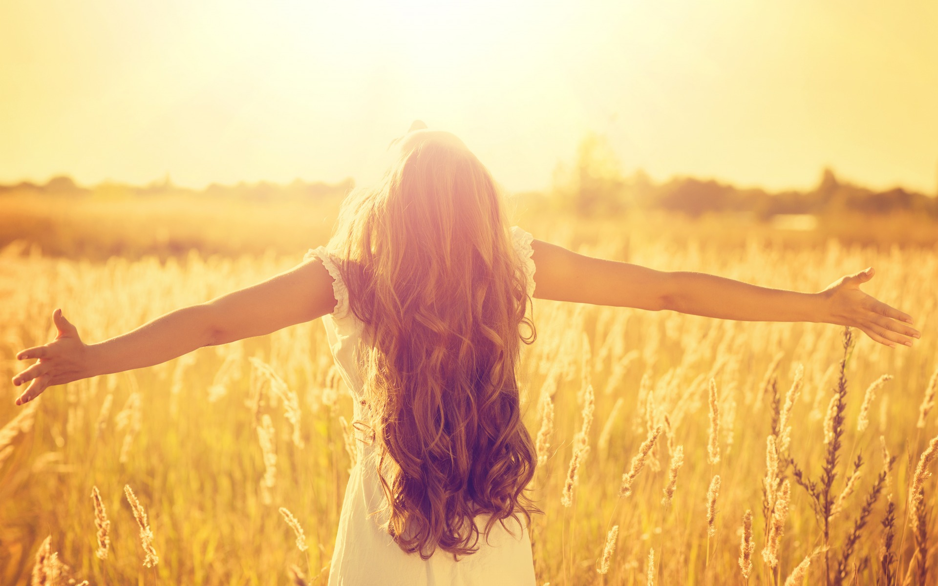 a-beautiful-girl-with-very-curl-long-hair-standing-on-the-wheat-field-in-sunshine-her-outstretched-arms-enjoys-the-freedom.jpg