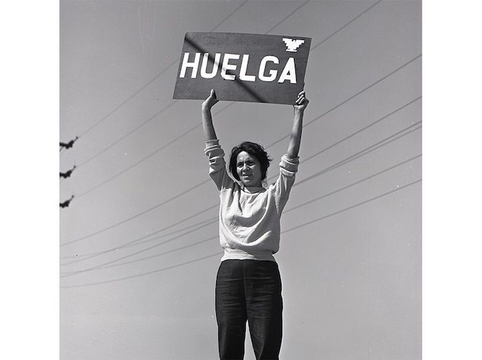 """Huerta holding up a sign that reads """"Strike,"""" 1960s."""