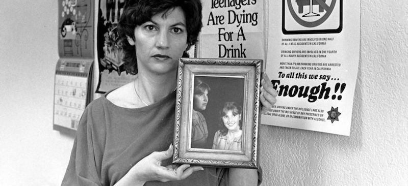 Lightner holding a photograph of her late daughter Cari, early 1980s.