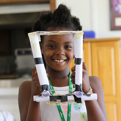 A child holds up a model bridge she built in STEM camp.
