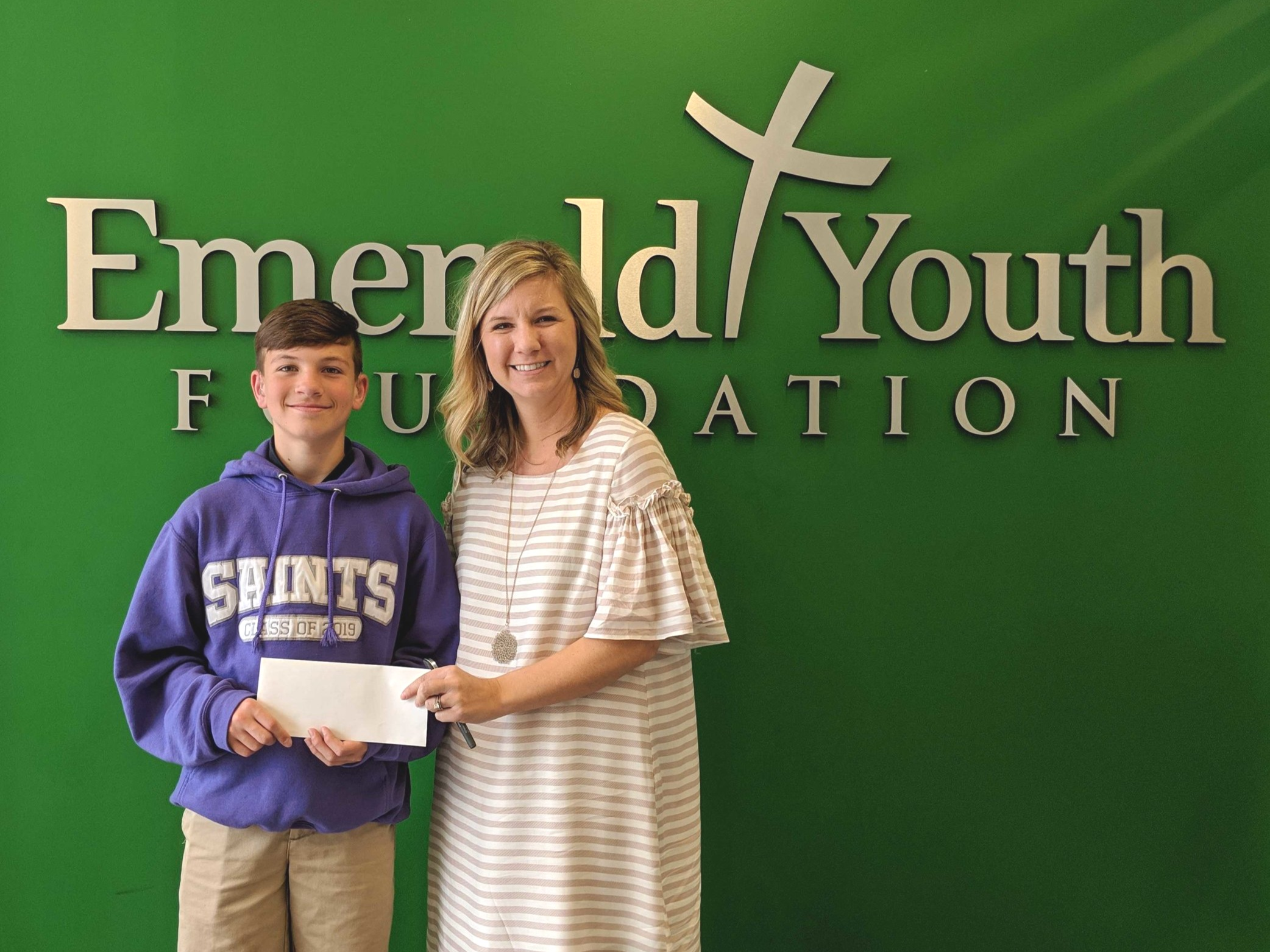 Episcopal School of Knoxville student Rockne Ullrich presents a donation to Emerald Youth Foundation's Haylee Marshall. Rockne raised the money through a school service project.