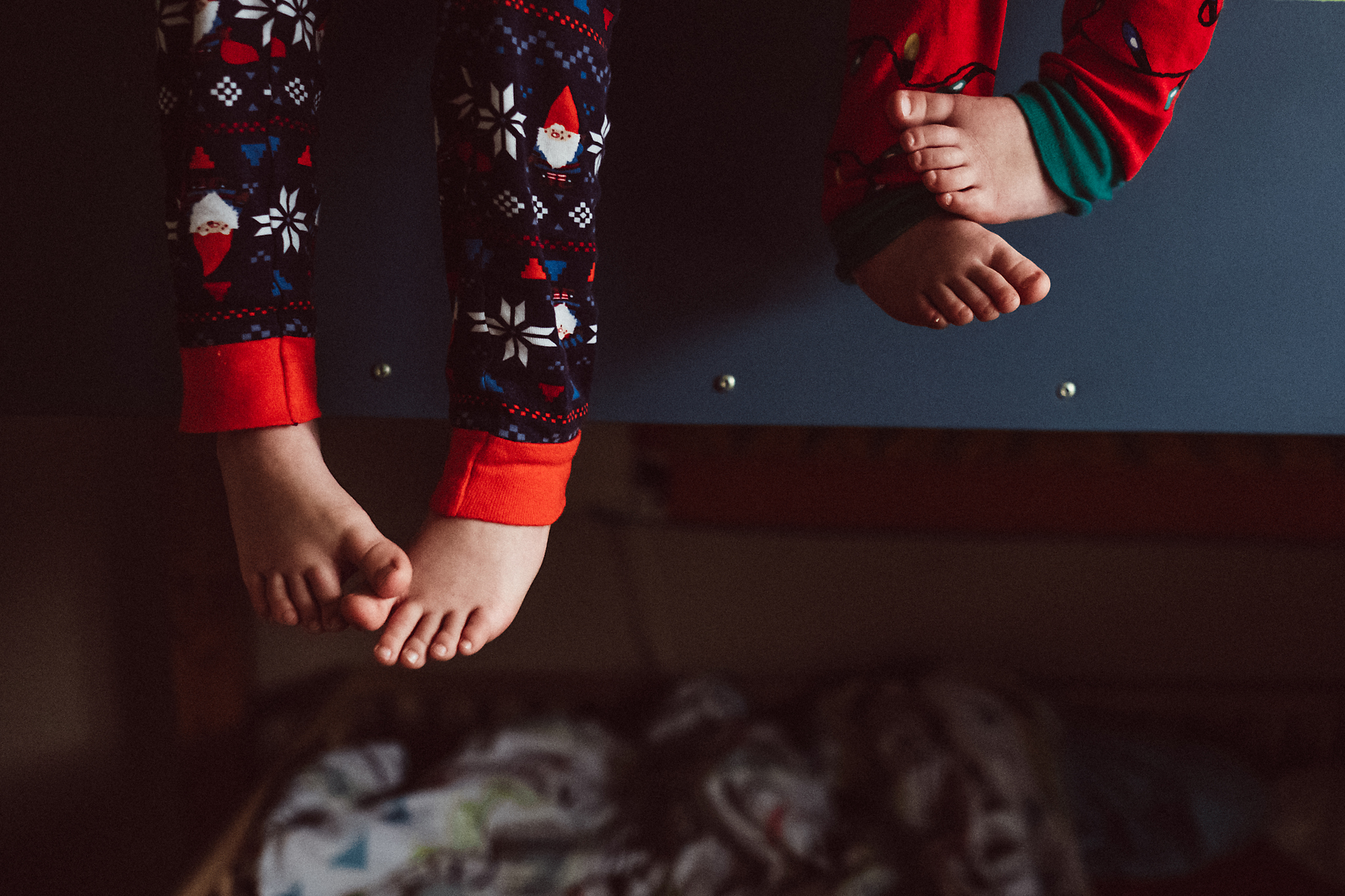 Feet in Christmas jammies hanging from loft bed