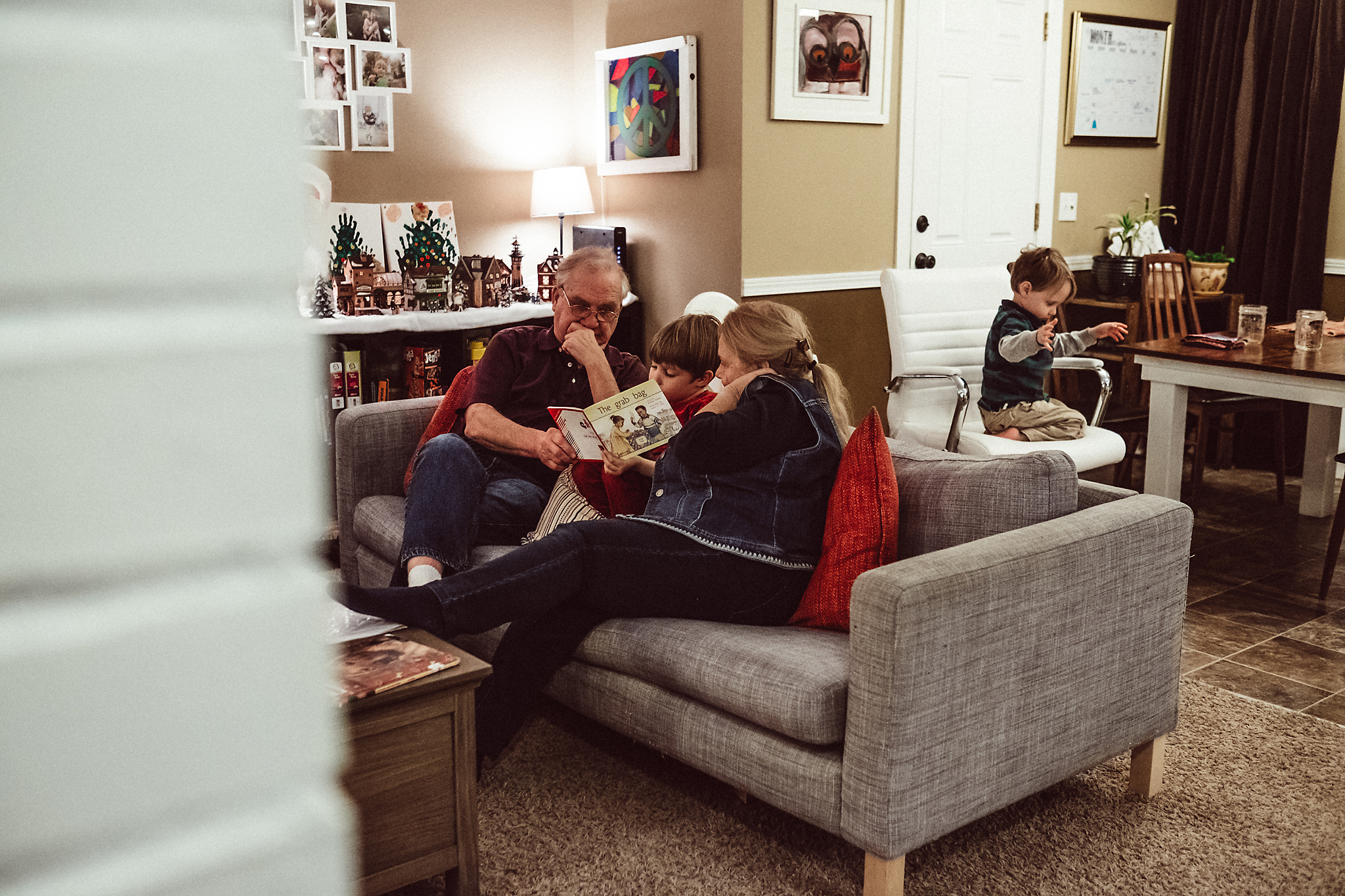 Grandparents and kids read story on couch